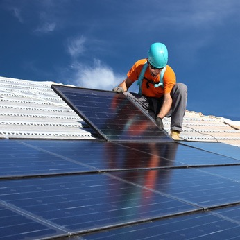 man installing solar panel on roof