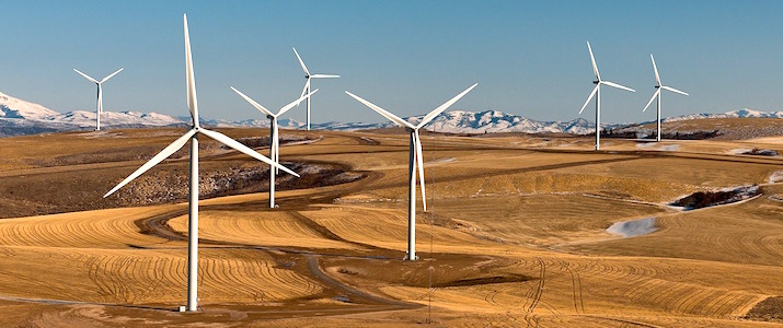 wind farm in the desert with mountains in the background
