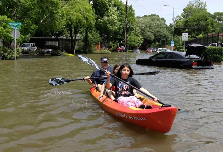 kids with grandparent in kayak on flooded street